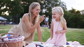 A family of two people, a mother and a small daughter, spends time together in a city park on a picnic. Young woman and. Little girl eating sweets, sitting on a stock footage