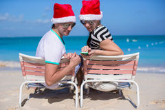 Family of two in Santa hats sitting on beach chair Royalty Free Stock Photos