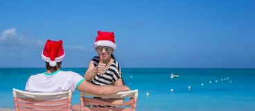 Family of two in Santa hats sitting on beach chair Royalty Free Stock Images