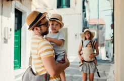 A family with two toddler children walking in town on summer holiday. A father and mother with son and daughter in baby carrier on a narrow street stock images