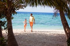 Family of two at vacation. Family of two, father and son, walking on empty beautiful white sand beach with palm trees and turquoise lagoon, family vacation Royalty Free Stock Photos