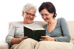 Family adult senior women having fun reading book Stock Images
