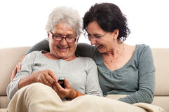 Family two women laughing with cell phone Royalty Free Stock Photo