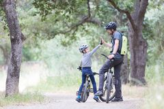 Family biking in the park. Family of two, young father and cheerful son, enjoying bike riding, kid giving high five to his dad, active family concept Royalty Free Stock Image