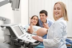 Family at ultrasound diagnosis, doctor smiling, posing. royalty free stock photography