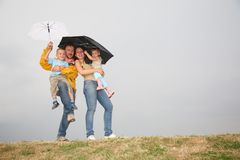 Family with the umbrellas Stock Images