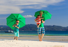 Family with umbrellas on tropical beach vacation. Father and kids with umbrellas on tropical beach vacation Stock Image