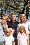 Family under apple tree in spring Royalty Free Stock Images