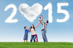 Family under cloud of 2015 in meadow Stock Photos