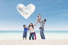 Family under heart cloud at beach Stock Photos