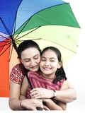 Family under protection. Mother and daughter with a single rainbow umbrella royalty free stock image