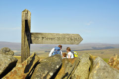 Family under signpost on top of hill. English countryside landscape shot during the Yorkshire Three Peaks Challenge - family leaned over a map, behind a sign Royalty Free Stock Photo