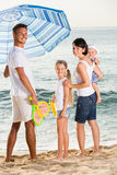 Family under sun umbrella on the beach Royalty Free Stock Images