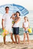 Family under sun umbrella on the beach Stock Images