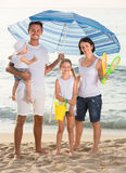 Family under sun umbrella on the beach Royalty Free Stock Photography