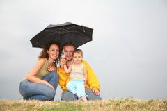 Family under umbrella. Family with the umbrella against gray sky Royalty Free Stock Images