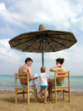Family under umbrella on beach royalty free stock image