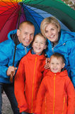 Family under umbrella in rainy day. Happy and colorful family under umbrella in rainy day Stock Images