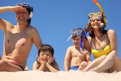 Family in underwater masks sit on sand Royalty Free Stock Photos