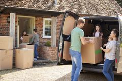 Family Unloading Boxes From Removal Truck On Moving Day stock photography