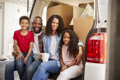 Family Unloading Boxes From Removal Truck On Moving Day royalty free stock images