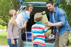 Family unloading car trunk while on picnic Stock Photography