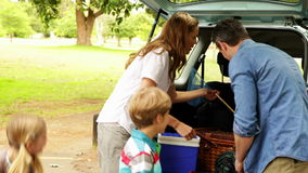 Family unloading their car for a camping trip stock footage