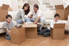 Family Unpacking Boxes Moving House. Family, parents, son and daughter, unpacking boxes and moving into a new home Royalty Free Stock Image
