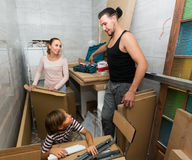 Family unpacking boxes with new furniture Stock Photos