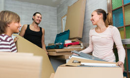 Family unpacking boxes with new furniture Royalty Free Stock Image