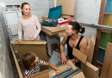 Family unpacking boxes with new furniture Royalty Free Stock Photography