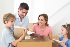 Family unpacking cardboard box in house Royalty Free Stock Photography