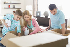 Family unpacking cardboard boxes in new house royalty free stock images