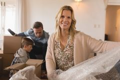 Family unpacking cardboard boxes in their new home stock image