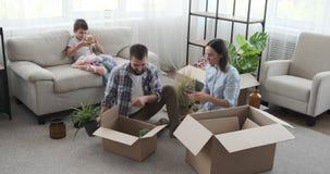 Family unpacking carton box in new apartment stock video