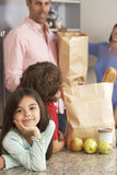 Family Unpacking Grocery Shopping In Kitchen Stock Image