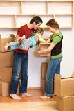 Family unpacking from lots of cardboard boxes Royalty Free Stock Photos