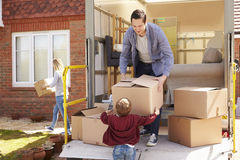Family Unpacking Moving In Boxes From Removal Truck royalty free stock image