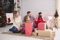 Family unwrapping christmas presents. Family sitting on carpet in living room unwrapping christmas presents Royalty Free Stock Images