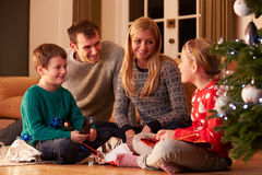 Family Unwrapping Gifts By Christmas Tree. At Home Smiling To Each Other Stock Photo