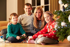 Family Unwrapping Gifts By Christmas Tree. Whilst Smiling at Camera Royalty Free Stock Photography