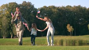 Family from USA waving backgrounds in the park, front view. Proud of military father and country stock footage