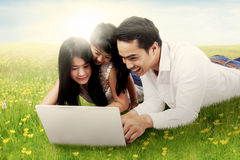 Family use laptop on grass Stock Image