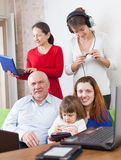 Family uses few various electronic devices Royalty Free Stock Photos