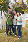Family using Cellphones. Single Mom with three teens standing outside on a beautiful day all looking at cellphones Stock Image