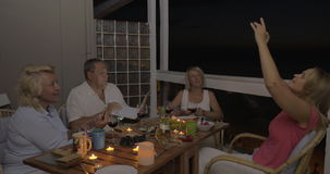 Family using cells and laptop during dinner stock footage