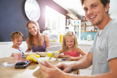 Family Using Digital Devices At Breakfast Table Stock Photography