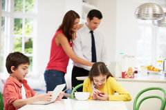 Family Using Digital Devices At Breakfast Table. NSmiling Stock Photos