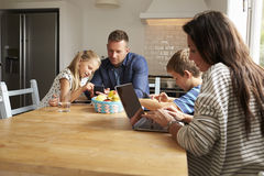 Family Using Digital Devices At Kitchen Table stock photos