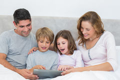 Family using digital tablet in bed Stock Photo